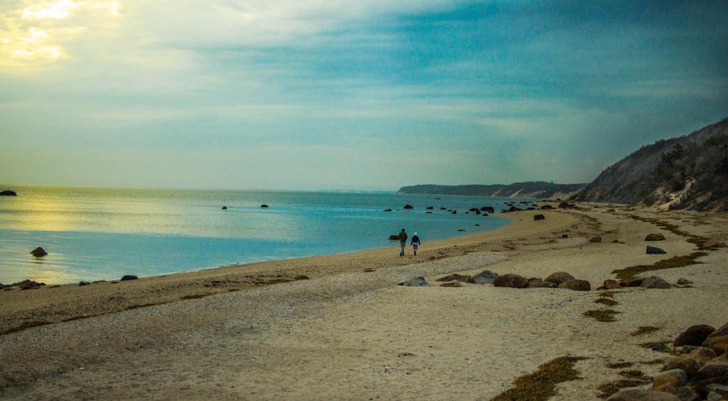 Two people walking on ocean beach with rocks